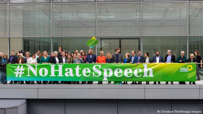 Members of Germany's Green Party stand behind a sign on which is written: #NoHateSpeech