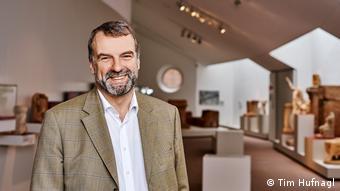 Der Archäologe Markus Reuter, ein freundlich lächelnder Mann mit grauem Bart in braunem Jackett, vor Exponaten des Rheinischen Landesmuseum in Trier, das er leitet