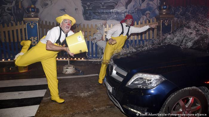 two clowns wash and throw water on a car