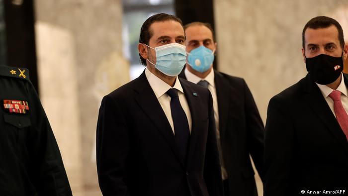 A masked Saad Hariri walking with other men in suits