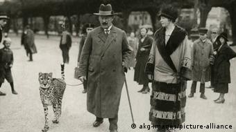 A man with a walking stick and woman on a walk with a cheetah in the 1920s in Berlin