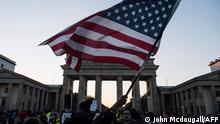 12.11.2016, Berlin, A demonstrator protesting against US president-elect Donald Trump waves a US flag during a demonstration at Berlin's Brandenburg Gate on November 12, 2016. (Photo by John MACDOUGALL / AFP)
