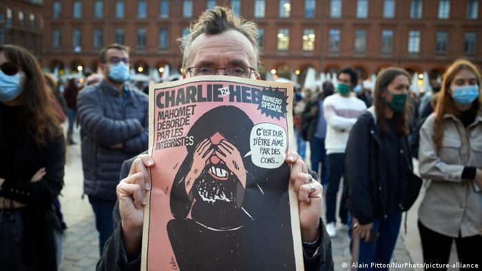 Мужчина с журналом Charlie Hebdo