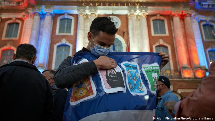 A man shows Charlie Hebdo cartoons pinned on a French flag in front of the townhall of Toulouse illuminated with the French colors