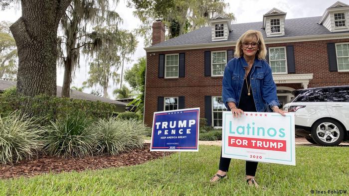 Mulher seguranda placa de apoio a Trump em um gramado ao lado de árvore, com casa ao fundo