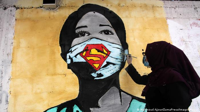 A Palestinian artist paints a mural of a medical worker wearing a Superman mask to help raise awareness of wearing face masks amid the coronavirus pandemic