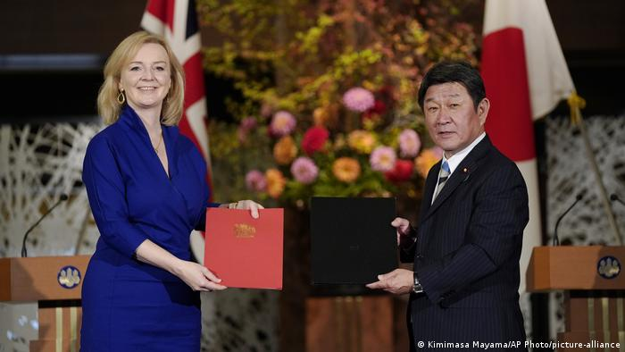 Liz Truss and Toshimitsu Motegi hold up the signed trade agreement