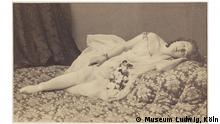 A black-and-white photo of a woman sleeping on a bed (Museum Ludwig, Köln)
