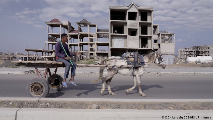A man on a horse carriage riding past a building in construction (Photo: DOK Leipzig 2020/Rift Finfinnee).