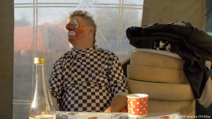 A man with clown make-up and a black-and-white checkered shirt, his head is turned to the side (photo: DOK Leipzig 2020/Joy).