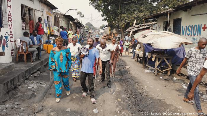 A group of people with crutches and a megaphone walk down a dirt street in Kinshasa (Photo: DOK Leipzig 2020/Downstream to Kinshasa).