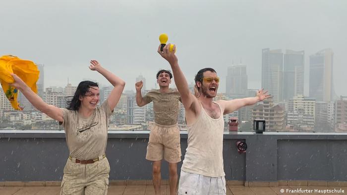 Drei Mitglieder der Kunstguerilla Frankfurter Hauptschule tanzend auf einem Hochhausdach; sie lachen, einer hält eine Skulptur von Joseph Beuys - eine Zitrone und eine gelbe Glühbirne - nach oben