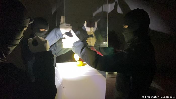 Schwarz maskierte Menschen heben eine Glasvitrine an, um eine Skulptur von Joseph Beuys - eine Zitrone und eine gelbe Glühbirne - zu entnehmen