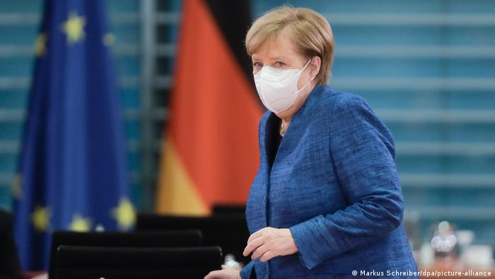 Merkel wearing a mask as she sits down for a Cabinet meeting