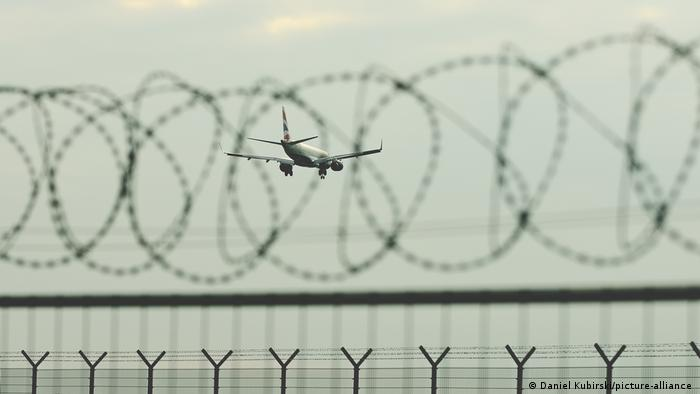 A plane flies over a barbed wire fence at Frankfurt Airport