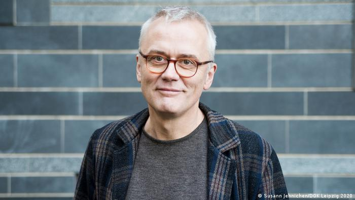 A portrait of Christoph Terhechte wearing a plaid jacket