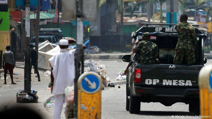 Military personnel drive along a street in Lagos