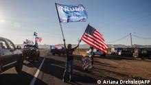 A woman waves a Trump and a US National flag as a caravan of cars from Kingman drives past supporting President Trump, as they gather for a presidential debate watch party, in Golden Valley, Arizona on October 22, 2020. (Photo by ARIANA DREHSLER / AFP)