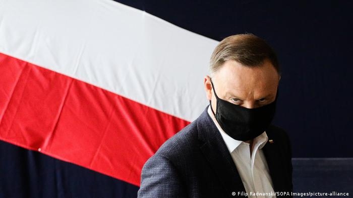 Andrzej Duda looks straight at the camera while wearing a face mask, with the Polish flag behind him