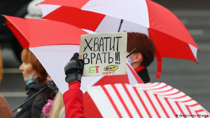 Участницы акции протеста в Минске с бело-красно-белыми зонтами