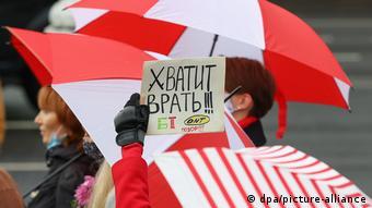 Участницы акции протеста в Минске с бело-красными зонтами и плакатом Хватит врать!