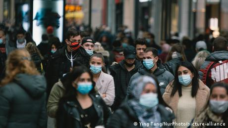 Crowd of people with face masks walking in the shopping block in Cologne (Ying Tang/NurPhoto/picture-alliance)