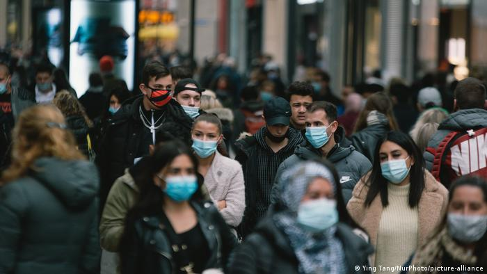 Crowd of people with face masks walking in the shopping block in Cologne