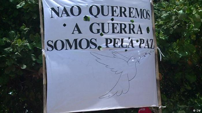 Mosambik Pemba | Plakat von FRELIMO. Anhänger ruft zu Frieden auf (Delfim Anacleto/DW)