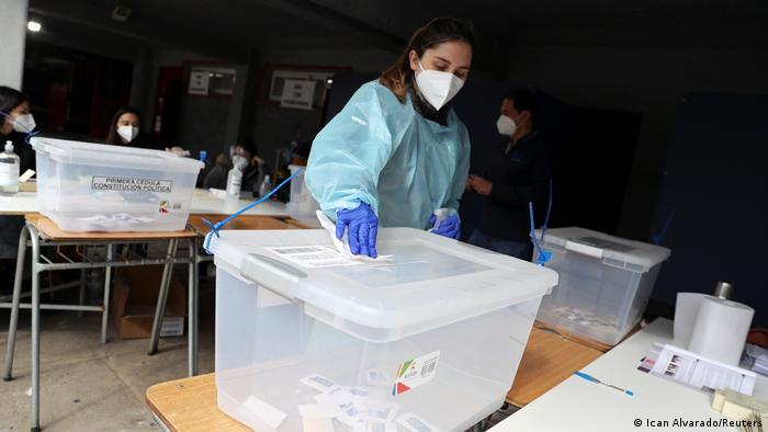 woman wearing a protective face mask and a suit disinfects a ballot box during a referendum on a new Chilean constitution