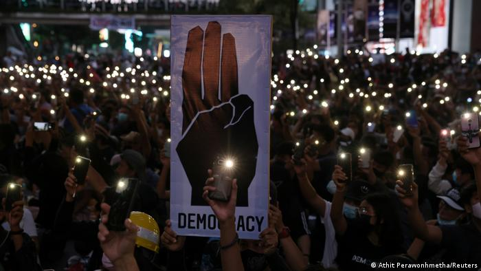 Pro-democracy protesters flash lights from their phones during an anti-government protest in Bangkok