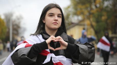Девушка с бело-красно-белым флагом на плечах показывает сложенное из ладоней сердечко