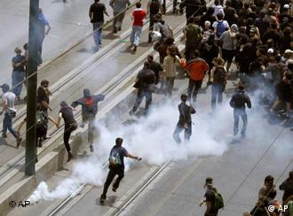 Demonstrators running away from tear gas during an anti-government rally in Athens