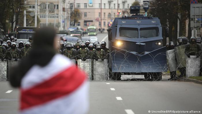 ПРотестующий с бело-красно-белым флагом на фоне омоновцев со щитами, колючей проволоки и спецмашины на акции протеста в в Минске, 25 октября