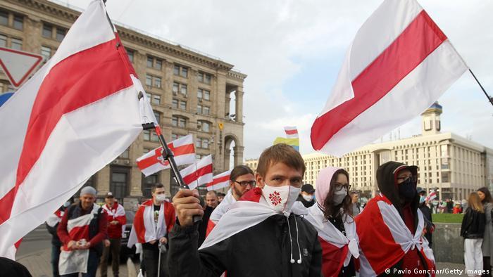 Протестующие с бело-красно-белыми флагами в Минске 25 октября