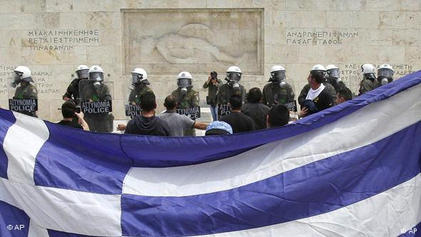 Protesters hold a Greek flag outside the Greek Parliament in Athens, Wednesday, May 5, 2010.
