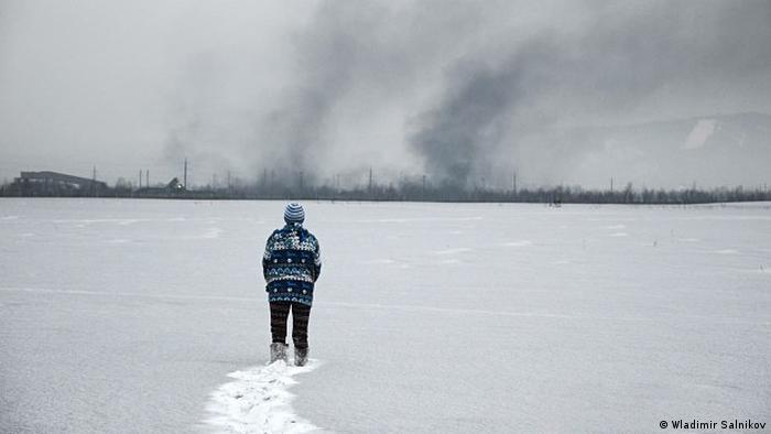 Мальчик идет по почерневшему снегу к угольному разрезу