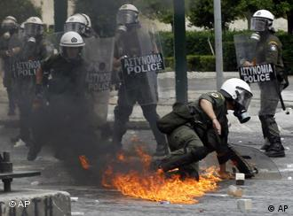 Riot police try to escape from a Molotov cocktail in central Athens, Wednesday, May 5, 2010.