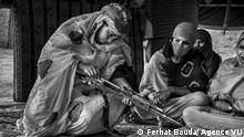 Eine junge Frau mit Kopftuch und in Hidschab baut eine Maschinenpistole zusammen und wird dabei von anderen Frauen beobachtet. (Ferhat Bouda/ Agence VU)