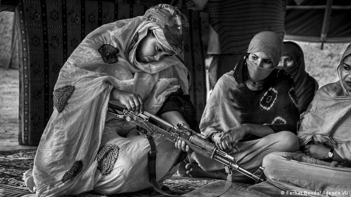 Eine junge Frau mit Kopftuch und in Hidschab baut eine Maschinenpistole zusammen und wird dabei von anderen Frauen beobachtet.