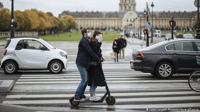 Two people ride a scooter in masks in Paris