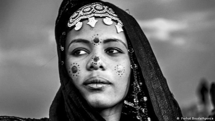 Junge Frau mit Stirnschmuck und Henna-Symbolen im Gesicht