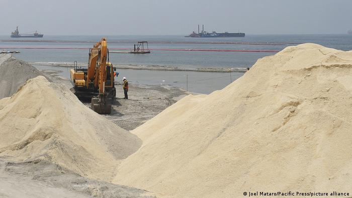 Workers and heavy equipment works on the shores of Manila Bay