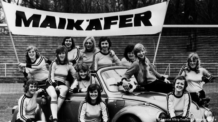 Female footballers posing in a car with a football