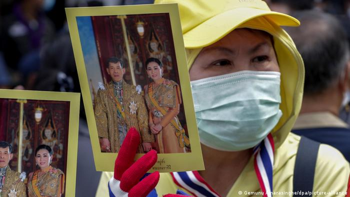 A Thai royalist holds up a photo of the king
