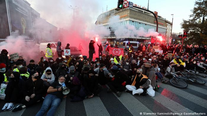Protesters sit on a city street in smoke to block cars