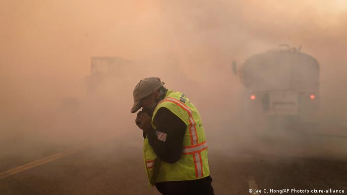 Hombre cubriéndose la cara del humo, causado por incendios en California