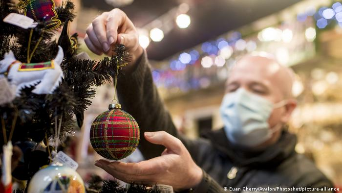 Shop owner hangs a Christmas bauble on a tree