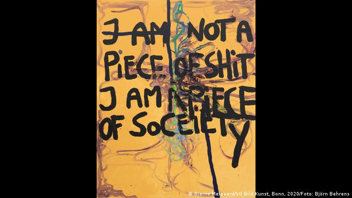 A yellow painting with graffiti-style painting on a canvas. I am not a piece of shit, I am a piece of society is written in large black letters in English. (Bjarne Melgaard/VG Bild-Kunst, Bonn, 2020/Foto: Björn Behrens)