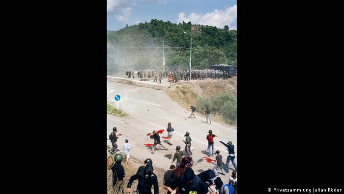 Protesters wearing black face off against police officers outside near a forest (Privatsammlung Julian Röder)