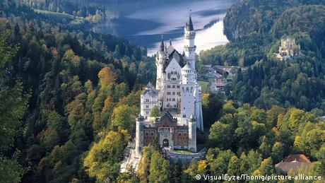 Aerial view of Neuschwanstein castle, with the Alpsee Lake in the background.